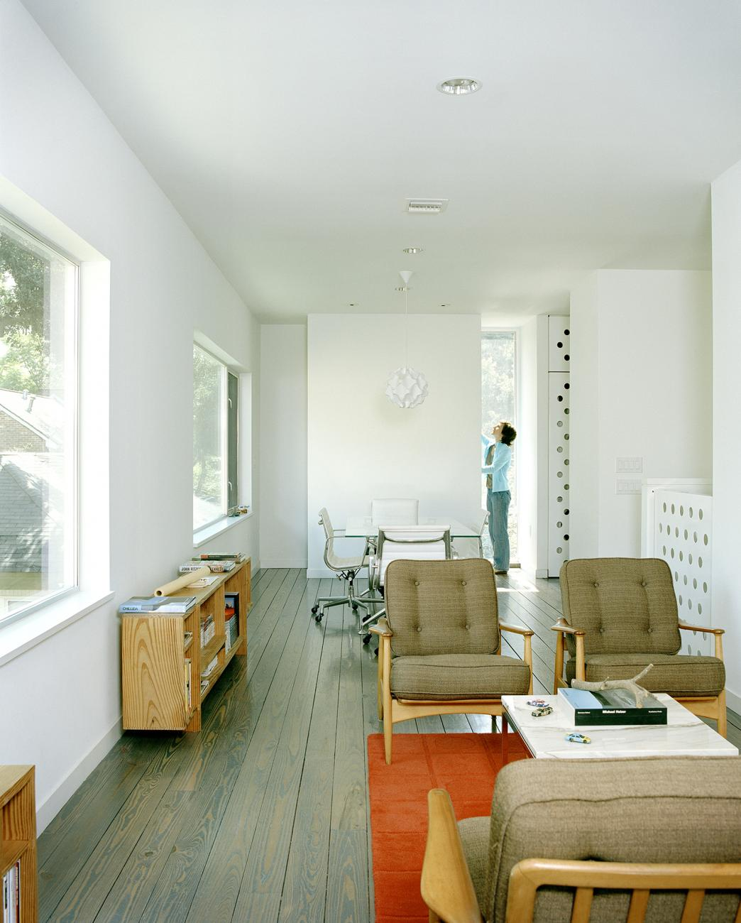 Second level living and dining areas with custom brake-form perforated steel guard rail and doors beyond
