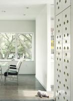 Custom brake-form perforated steel doors and concealed storage adjacent to dining area